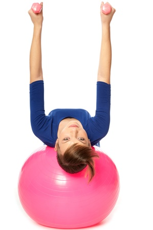 balance ball: Instructor taking exercise class using ball and dumbbells at gym