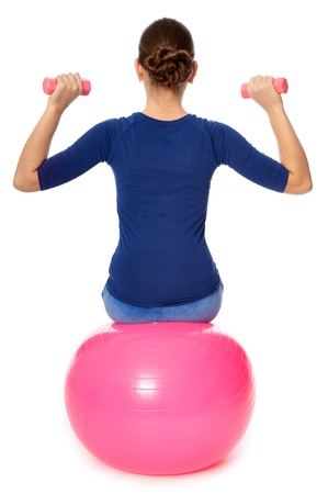 strength therapy: Instructor taking exercise class using ball and dumbbells at gym