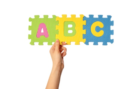 mother showing childrens educational colored puzzles with ABC letters to her child photo