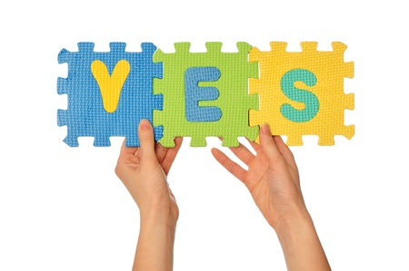 teacher holding in the hand the amusing colored educational puzzles with the word yes Stock Photo - 8806615