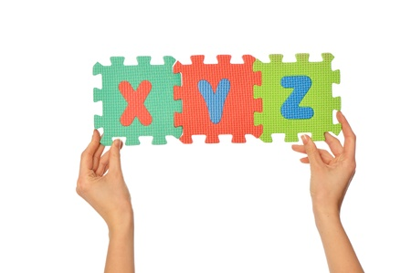 xyz: Teacher holding in the hand the amusing colored educational puzzles with alphabet