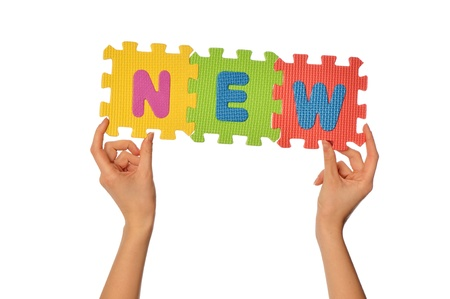 teacher holding in the hand the amusing colored educational puzzles with the word new Stock Photo - 8903146