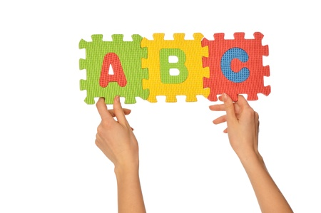 Teacher holding in the hand the amusing colored educational puzzles with alphabet Stock Photo - 9321297