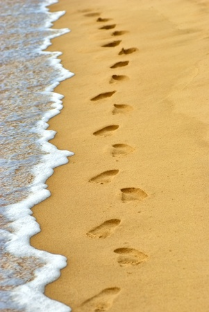 Ocean wave wash away human footprints on sand at the beach photo
