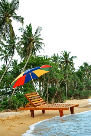 umbrella and lounge chair on the shore of exotic island with palm trees photo