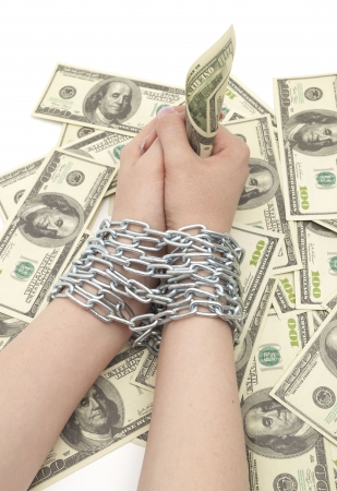 hands with dollar are bound by chain