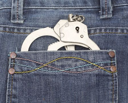 militiaman: handcuffs in jeans pocket Stock Photo