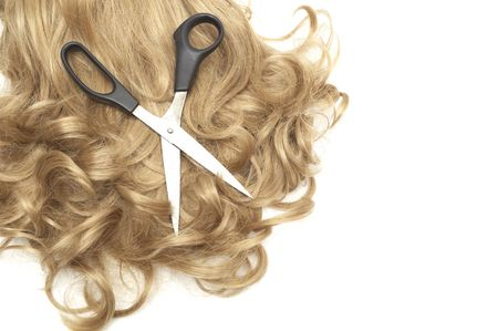 long blond human hair close-up and scissors photo