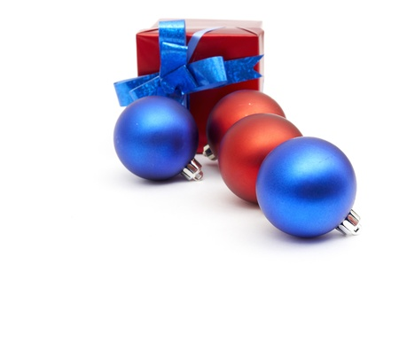 matt christmas balls and a gift in red wrapping on white photo