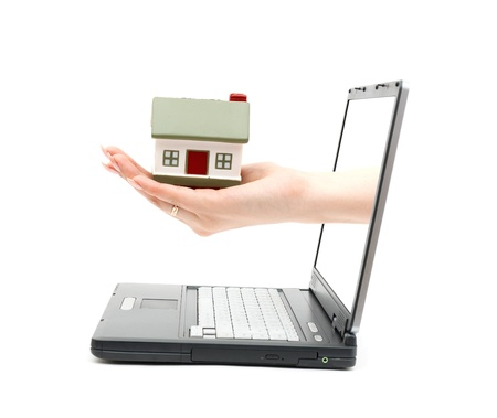 Womens handfrom laptop with a little house isolated on white