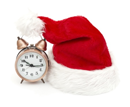 Alarm clock on the hat of Santa Claus isolated photo
