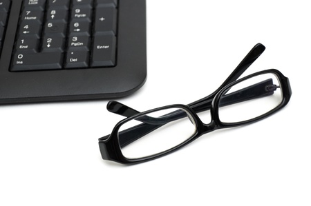 learnt: glasses on computer keyboard isolated on white
