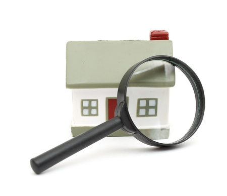 magnifying glass examining model home. Isolated on white. Stock Photo - 8539405
