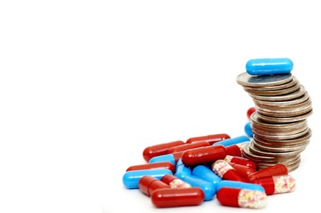 Rising stack of quarters and drugs signifying rising cost of medicine. Stock Photo - 8540046