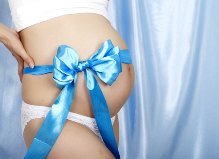 Young and happy beautiful pregnant woman with blue ribbon and bow over her belly, photo