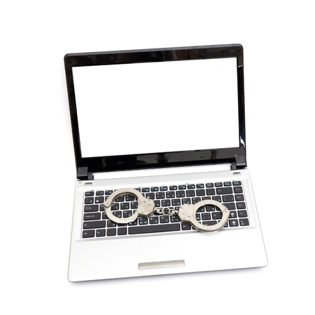 Handcuffs is on the laptop keyboard. Computer/Internet crimes and internet addiction concept. Stock Photo - 8539743