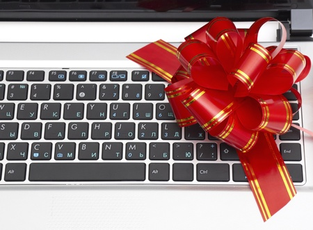 Gift laptop (red bow) isolated on white background photo
