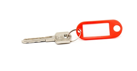 certitude: House key with blank label isolated on white background Stock Photo