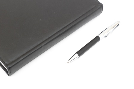 black leather Notebook and pen. isolated on white photo