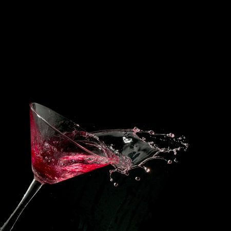 red martini cocktail splashing into glass on black background Stock Photo - 8918153