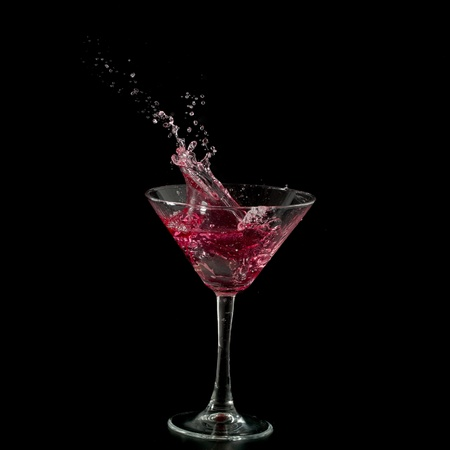 abstract liquor: red martini cocktail splashing into glass on black background
