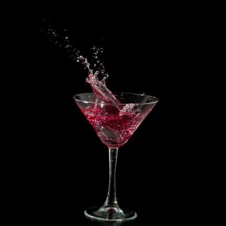 red martini cocktail splashing into glass on black background Stock Photo - 8918152