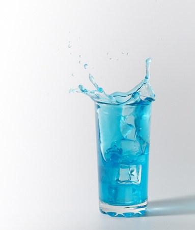 blue splash in glass from ice cube Stock Photo