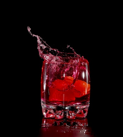 red splash in glass from ice cube photo