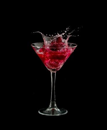 copa de martini: martini rojo c�ctel salpicadura en vidrio sobre fondo negro Foto de archivo