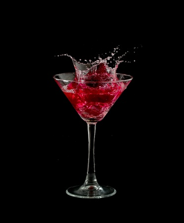 martini splash: red martini cocktail splashing into glass on black background