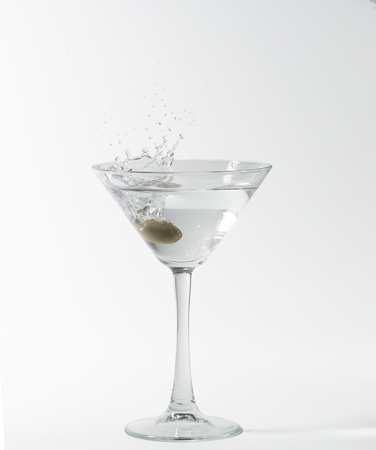 martini cocktail splashing into glass on white background photo