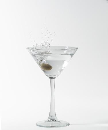 martini cocktail splashing into glass on white background photo