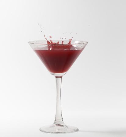 red martini cocktail splashing into glass on white background photo