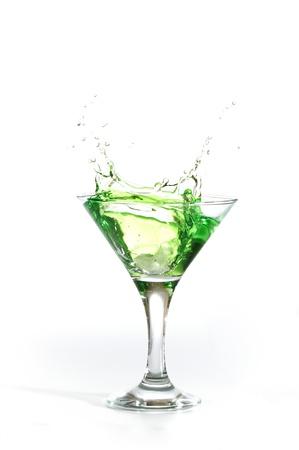 green martini cocktail splashing into glass on white background photo