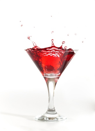 red martini cocktail splashing into glass on white background Stock Photo - 9049142