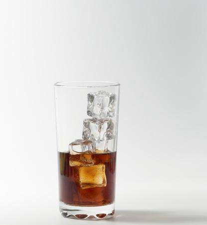carbonation: Vidrio de cola con hielo en el fondo blanco