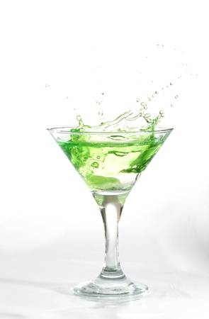 green martini cocktail splashing into glass on white background