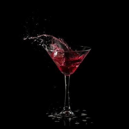 red martini cocktail splashing into glass on black background Stock Photo - 9049176