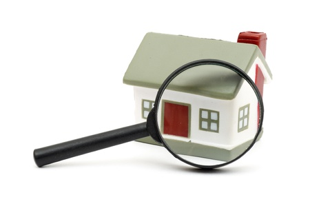 magnifying glass examining model home. Isolated on white. photo