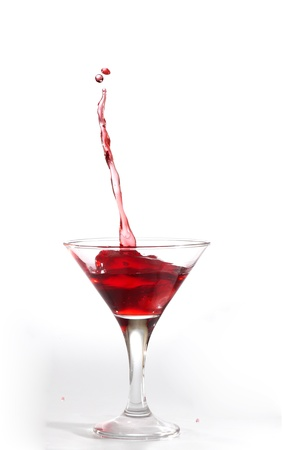 abstract liquor: red martini cocktail splashing into glass on white background