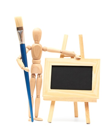 artists dummy: Wooden artist mannequin with brush in pose with wood frame Stock Photo