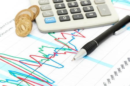 Calculator, coins and pen laying on chart. Concept of finance. photo