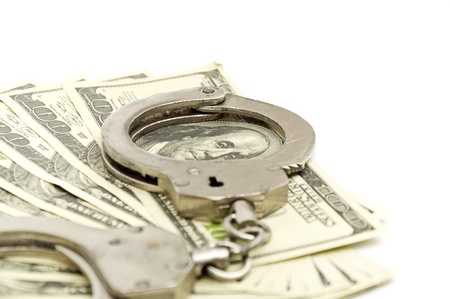 Handcuffs on money background, business security concept photo