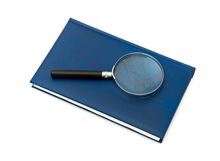 Magnifying glass and book isolated on white background photo