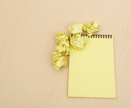 Notebook and crumpled paper on wooden table photo