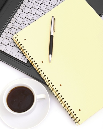 A cup of coffee on a laptop on white background photo