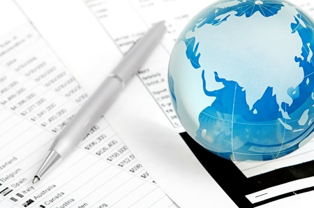Glass globe on chart background  with pen photo
