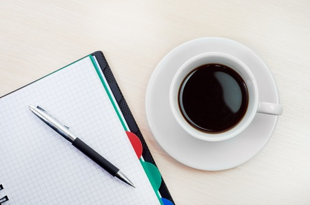 Coffee cup note book on table with pen photo