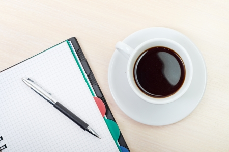 blank newspaper: Coffee cup with note book on table Stock Photo