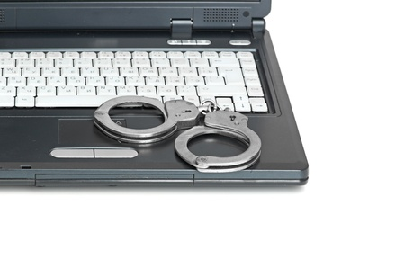 Handcuffs is on the laptop keyboard  Computer Internet crimes and internet addiction concept  Stock Photo - 13913251